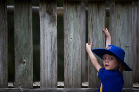 Primary school student in hat and uniform, climbing a fence and looking pensive.