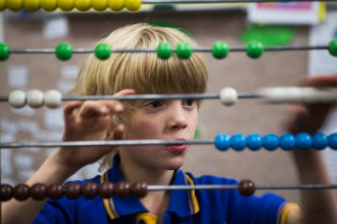 Primary school student playing with coloured abacus.